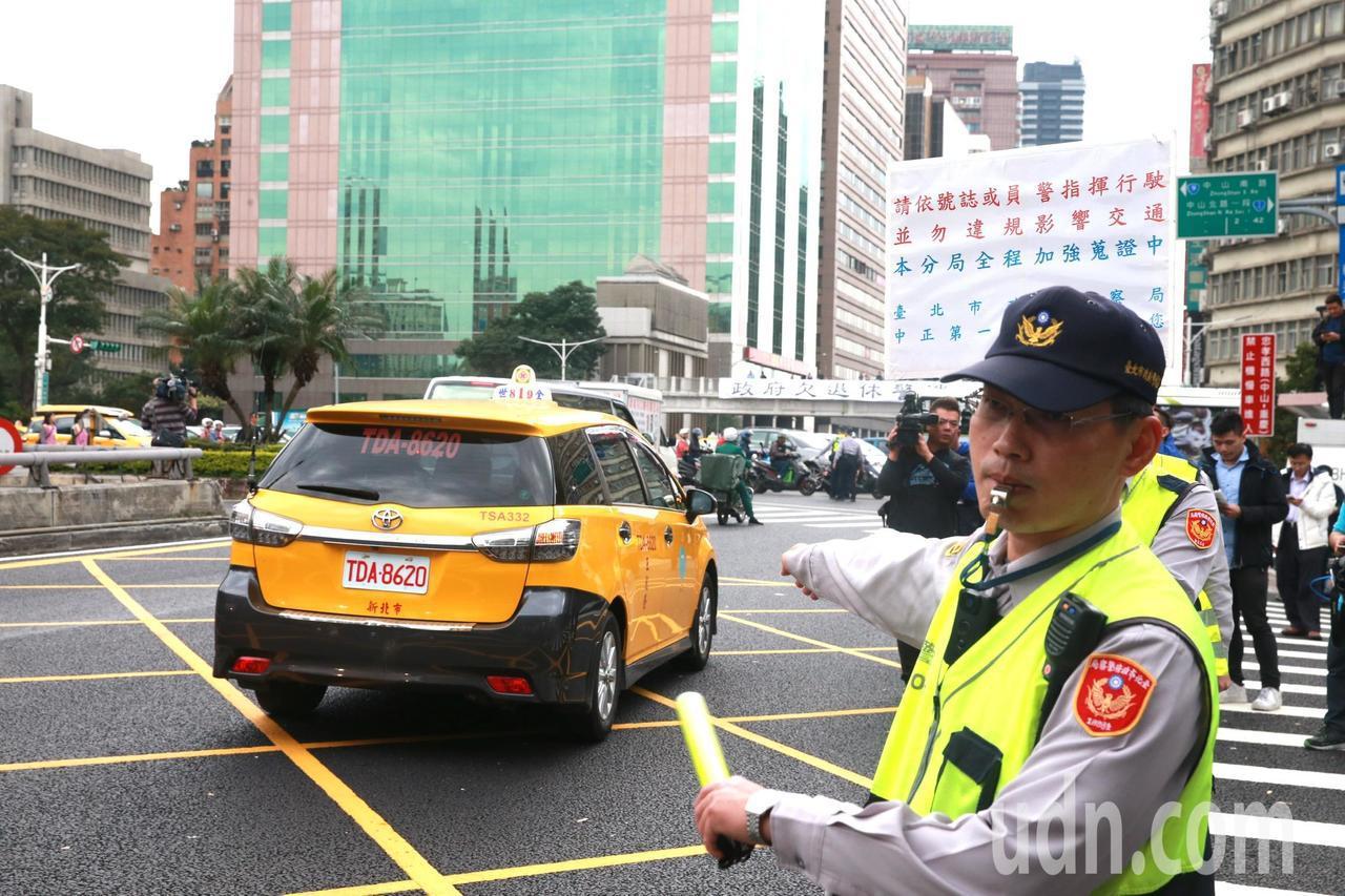 計程車司機繞行行政院周邊道路抗議,警方在旁疏導交通,舉牌柔性勸導。記者黃義書/攝...