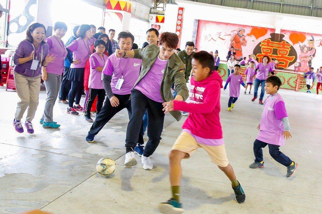 溫昇豪關懷偏鄉部落孩子,和小朋友們踢足球。圖/療癒之手基金會提供