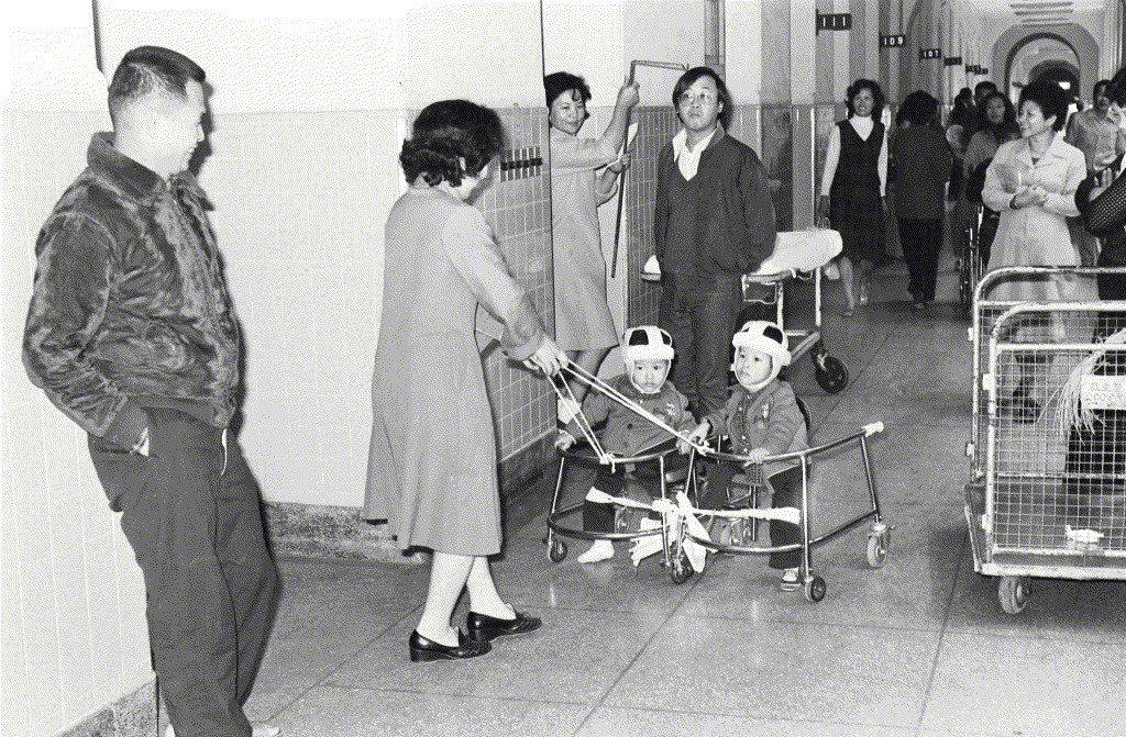 分割手術成功的連體嬰張忠仁、忠義兄弟戴著特製安全帽,利用學步車上的支架作為支力點...