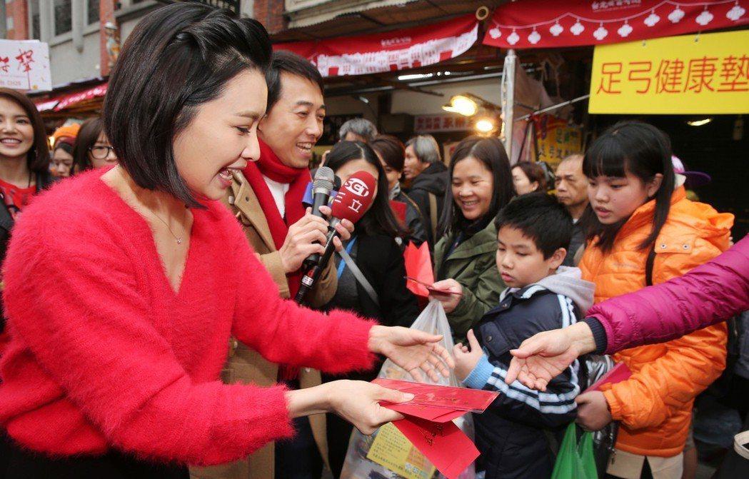 三立《炮仔聲》演員吳婉君到迪化街年貨大街掃街賀年發紅包袋。記者徐兆玄/攝影