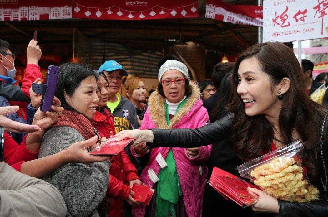 三立《炮仔聲》演員王宇婕到迪化街年貨大街掃街賀年發紅包袋。記者徐兆玄/攝影