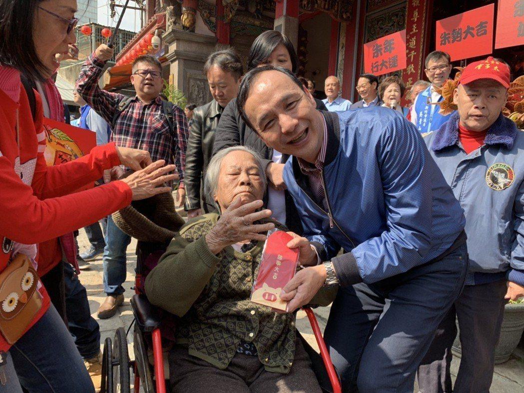 朱立倫(左)昨在新竹市關聖帝君廟發紅包袋,年約8旬行動不便婆婆,搶到紅包袋頭香。...