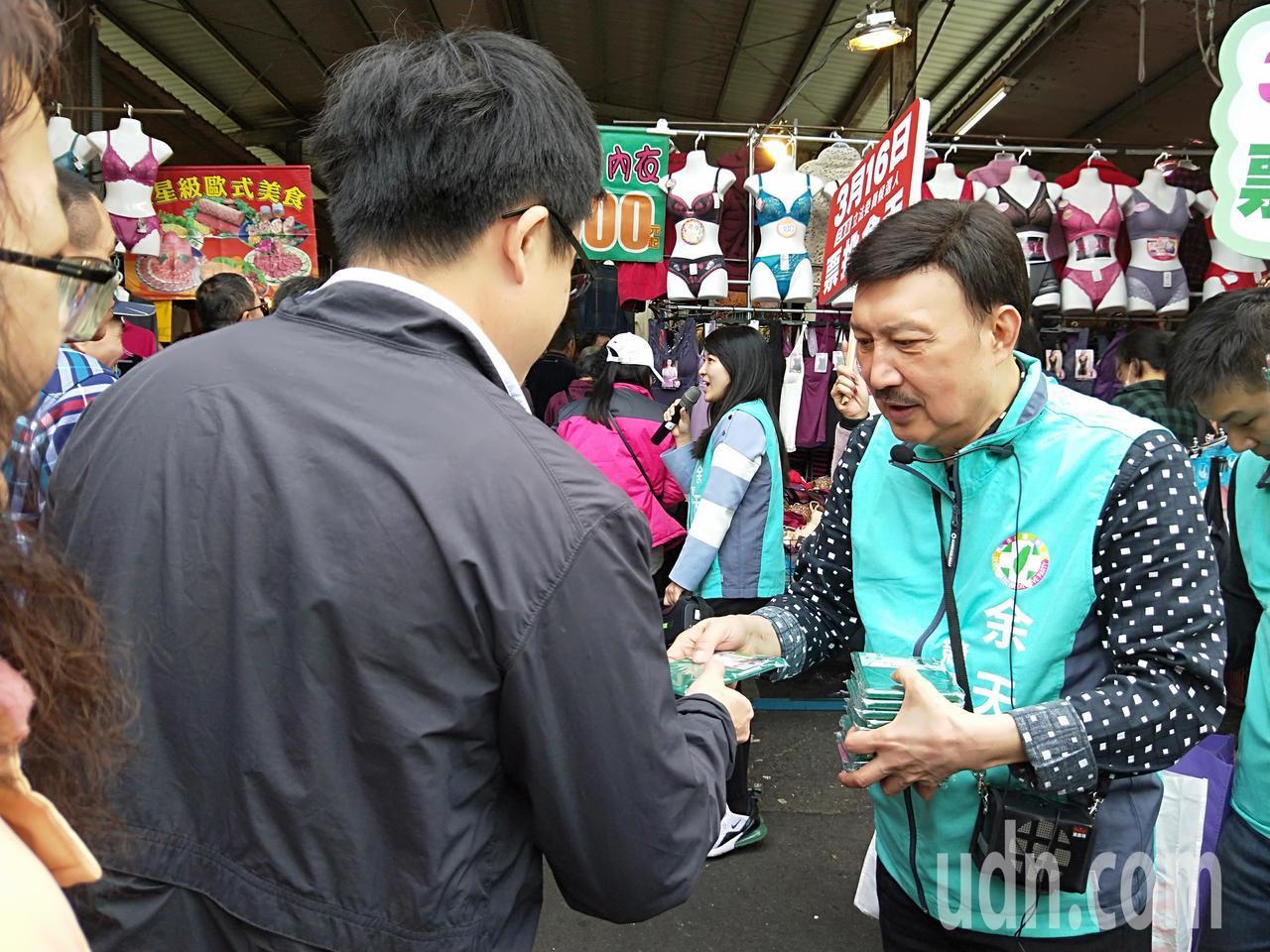余天(右)到力行市場掃街,發送文宣品菜瓜布。記者施鴻基/攝影