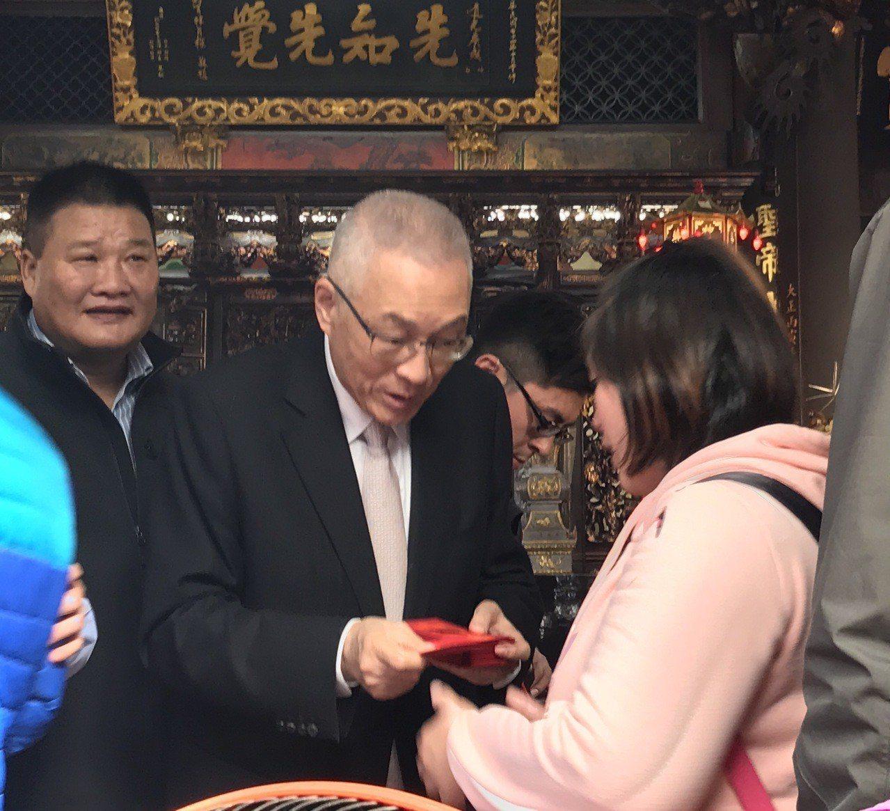 國民黨主席吳敦義今天下午到三重先嗇宮參拜並發送福袋。記者陳珮琦/攝影