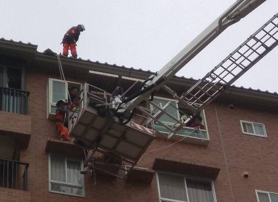 宜蘭縣政中心附近凱旋社區,有名婦人站在8樓遮雨台,狀甚驚險,消防隊員透過垂降、窗...