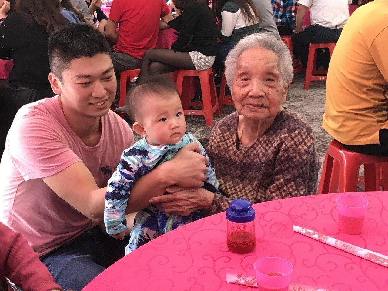 年紀最長的101歲張楊嬌娥(右)今天中午開心抱9個月的曾孫張紘睿(中),家族開心...