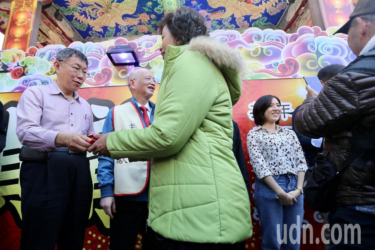 台北市長柯文哲(左一)上午到關渡宮參拜及發紅包,副發言人黃瀞瑩(右一)也現身陪同...