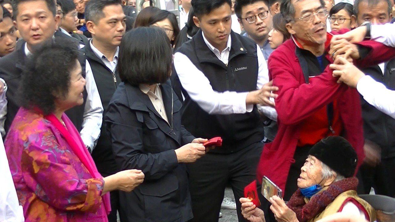 一名抗議男子(右、穿紅色外套)混在領紅包的人群中,拿出預藏的麥克風嗆蔡總統,高喊...