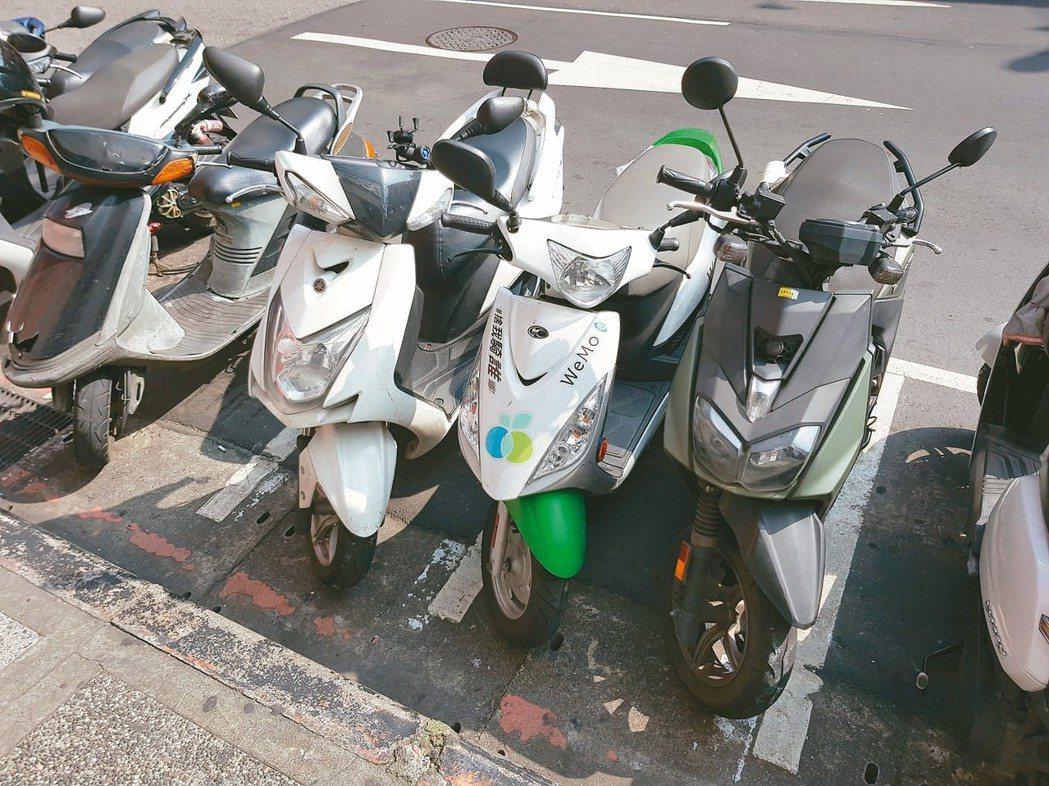 台北鬧區商圈機車格常見「車擠車」、「2格停3車」,不按分隔標線停放機車。 記者翁...