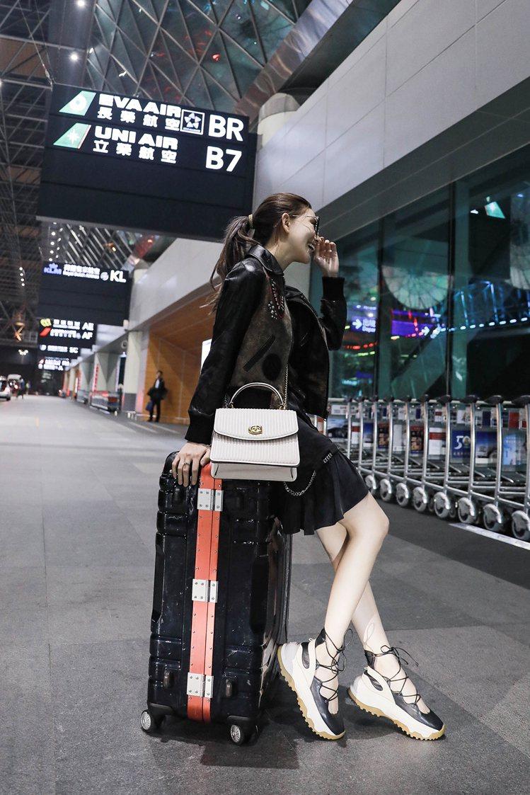 昆凌選穿Coach 2019春季女裝系列的連身裙秀出美腿,搭配同系列皮夾克和綁帶...
