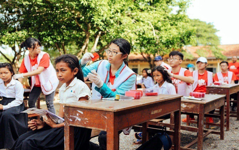 去年暑假,台北醫學大學的青年深入柬埔寨偏鄉,為當地孩童抓頭蝨。圖/教育部提供