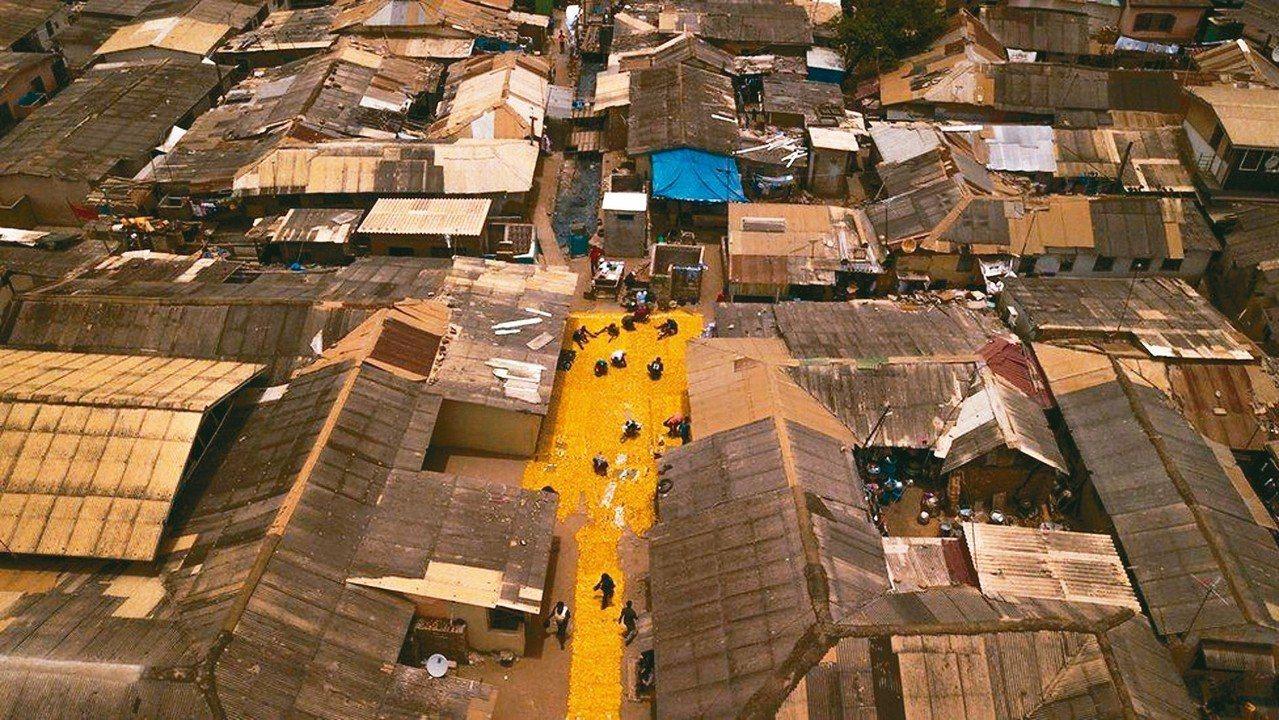 迦納拉區居民協力鋪設黃磚路。 圖/取自BBC網站