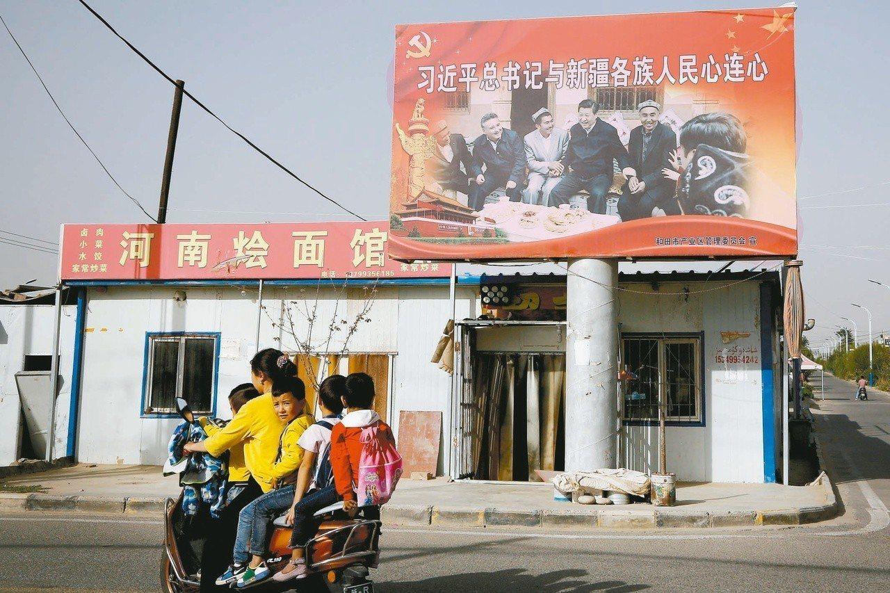 新疆民宅的看板上有習近平與維吾爾族握手的照片。美聯社