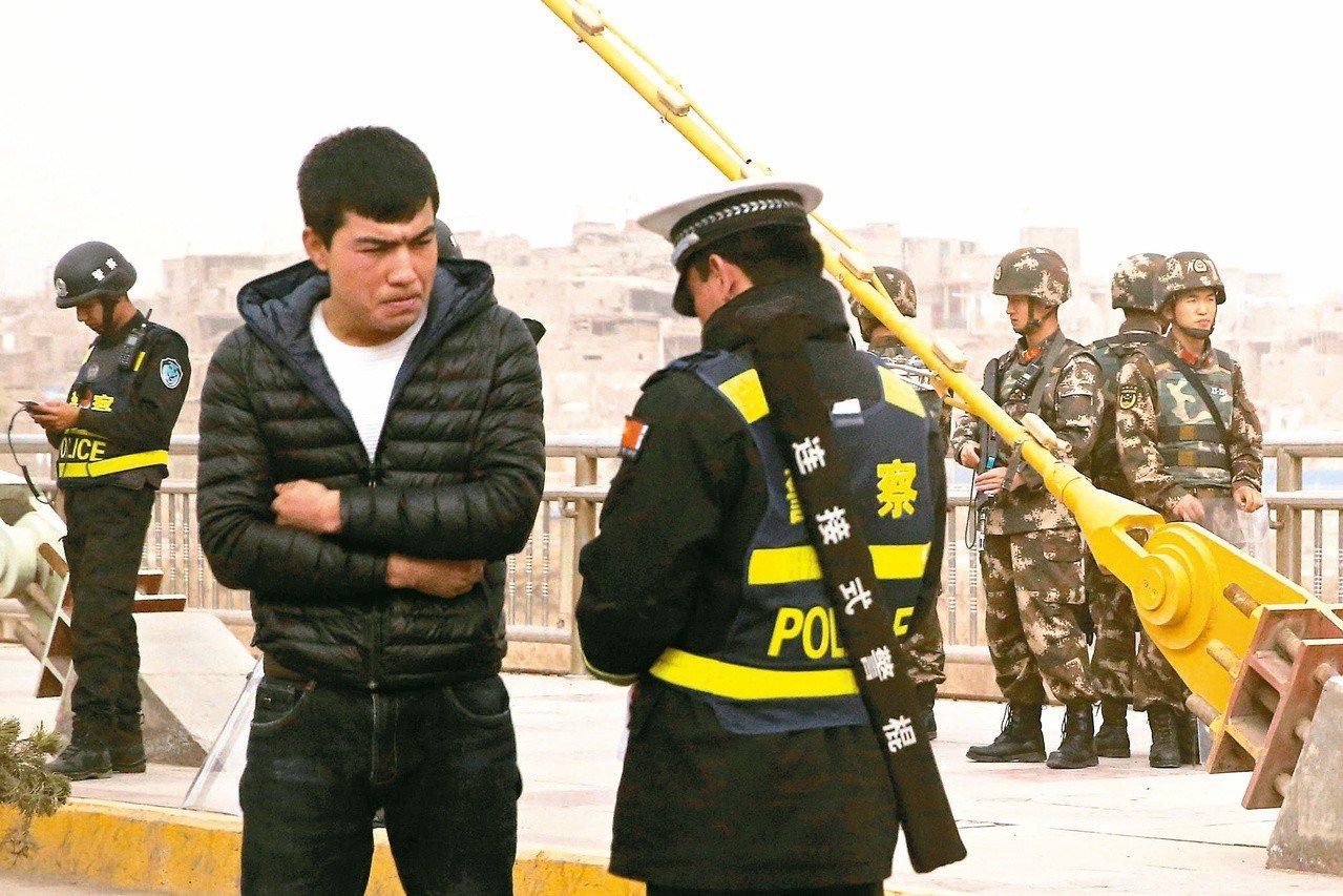 南疆喀什街道上,警察正在確認一名男子的身分證。路透