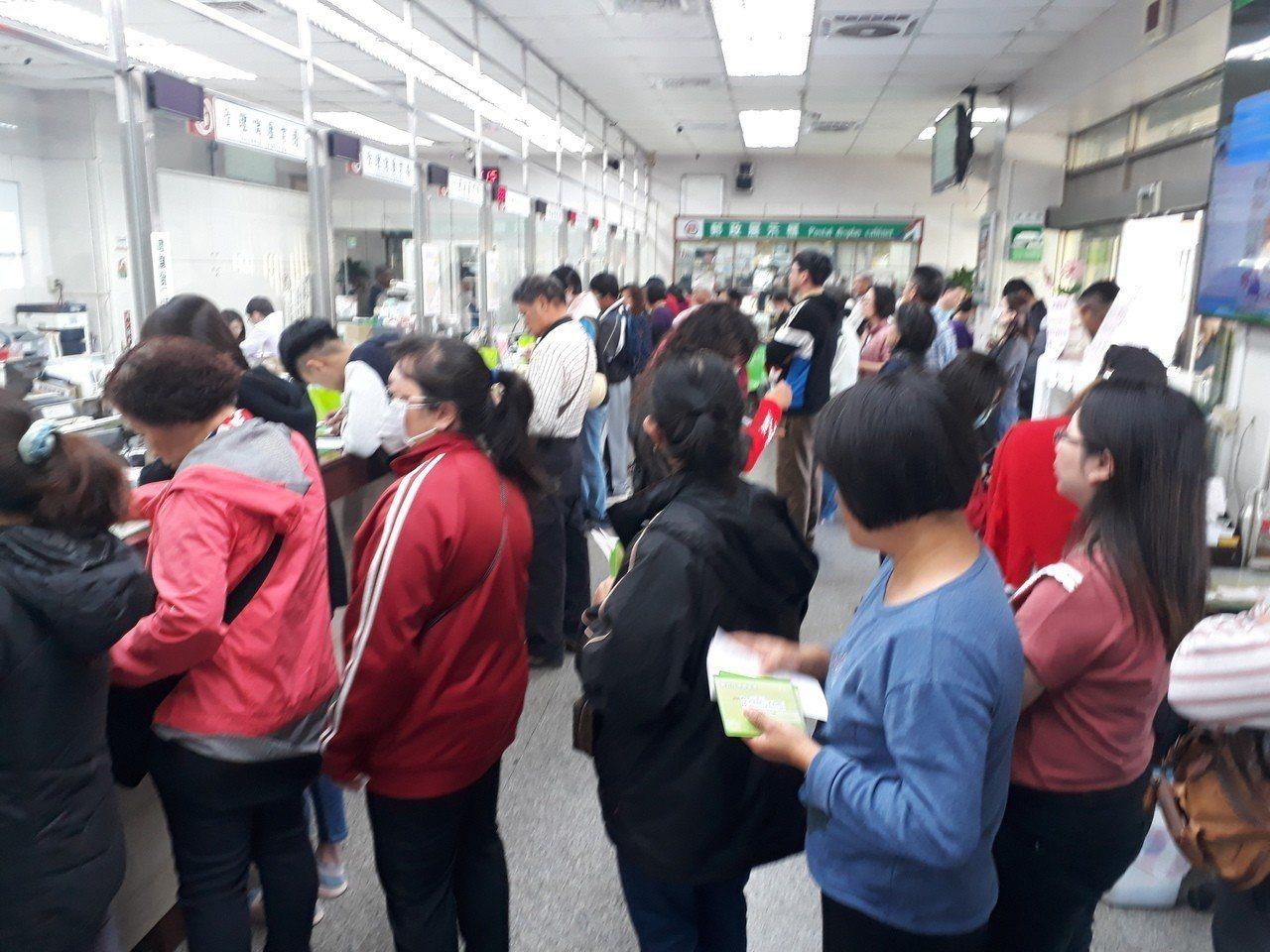 部分郵局今天一大早直到下午接近下班時間依舊人潮洶湧郵局外車輛停到大馬路上。記者周...