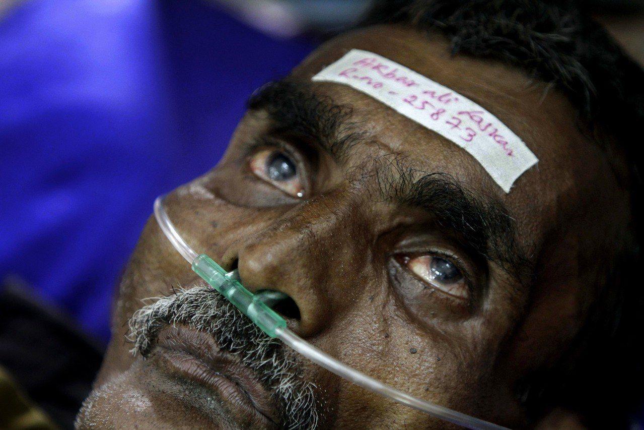 印度鄉間流行飲用便宜的私釀酒,不時發生假酒中毒案,圖為一名男子因甲醇中毒住院治療...