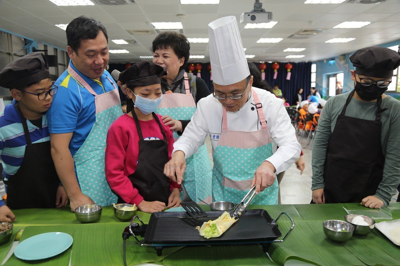 昨天是開學日,台北市教育局長曾燦金(右二)一早到中山區大佳國小陪學童親手做早餐,...
