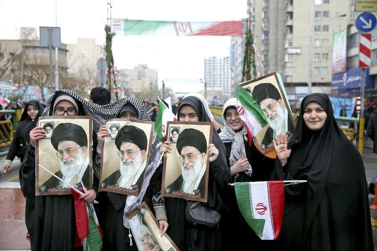 慶祝伊斯蘭革命40周年,伊朗婦女也拿著革命英雄何梅尼的海報,上街遊行。(美聯社)