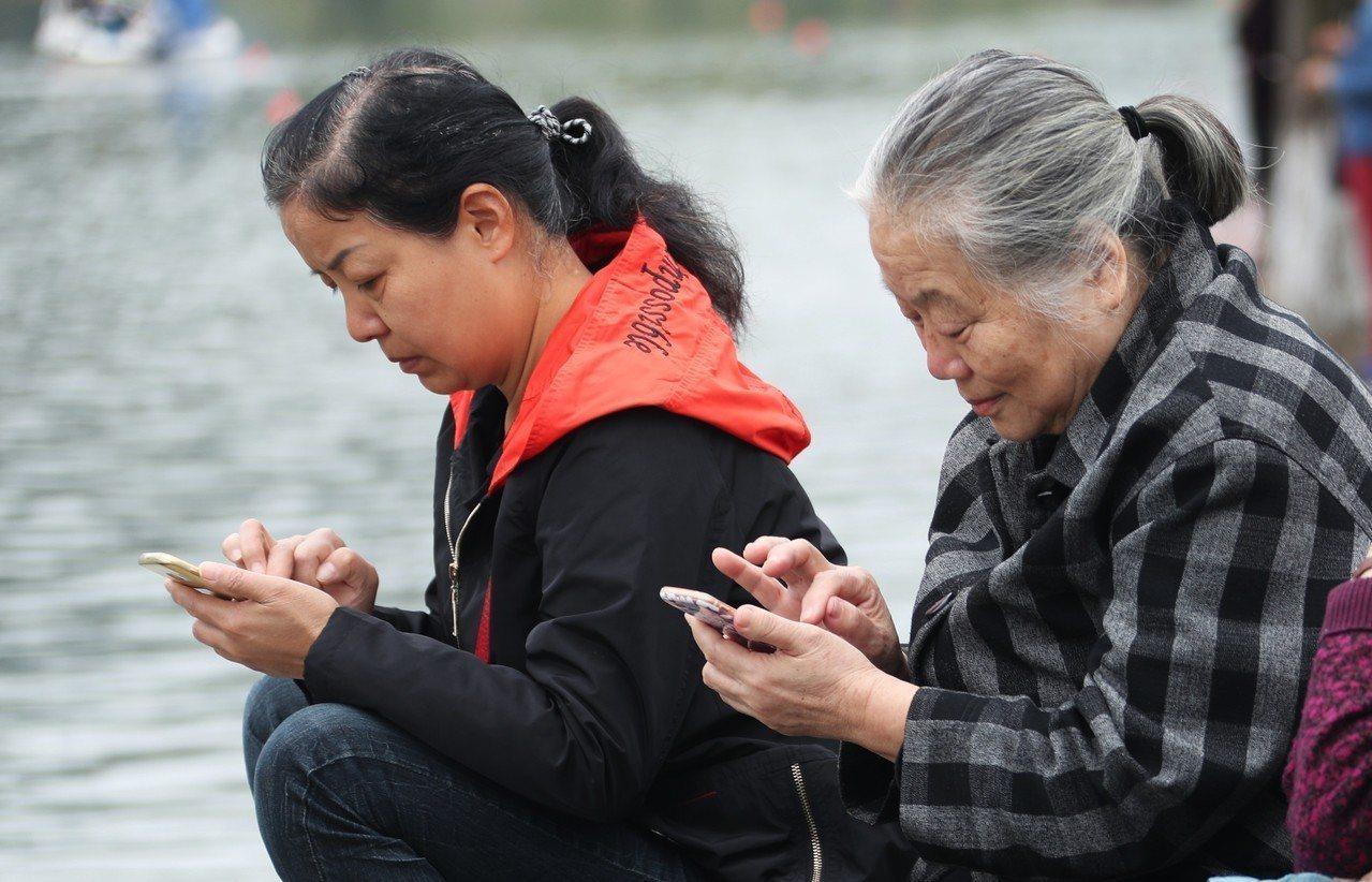 中國長輩也成為低頭族。 世界日報