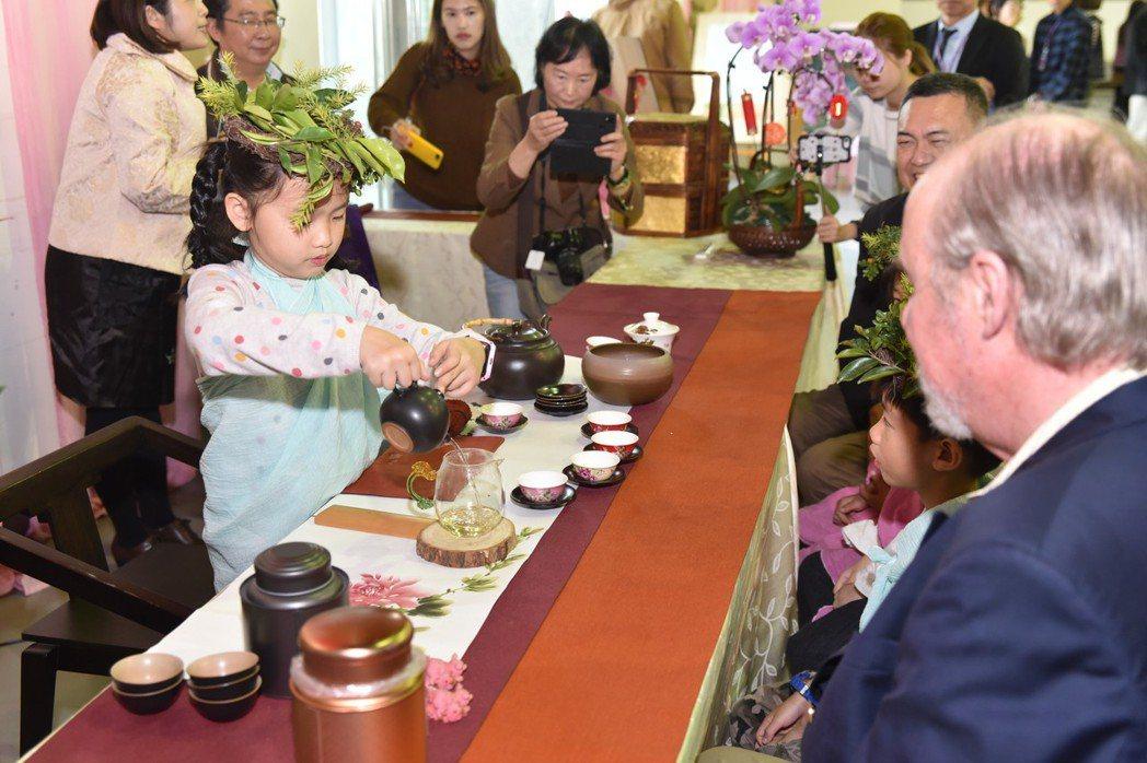 小朋友化身小茶師奉茶給現場來賓與托爾倫‧芬瑟博士。 黃啟銘/攝影。
