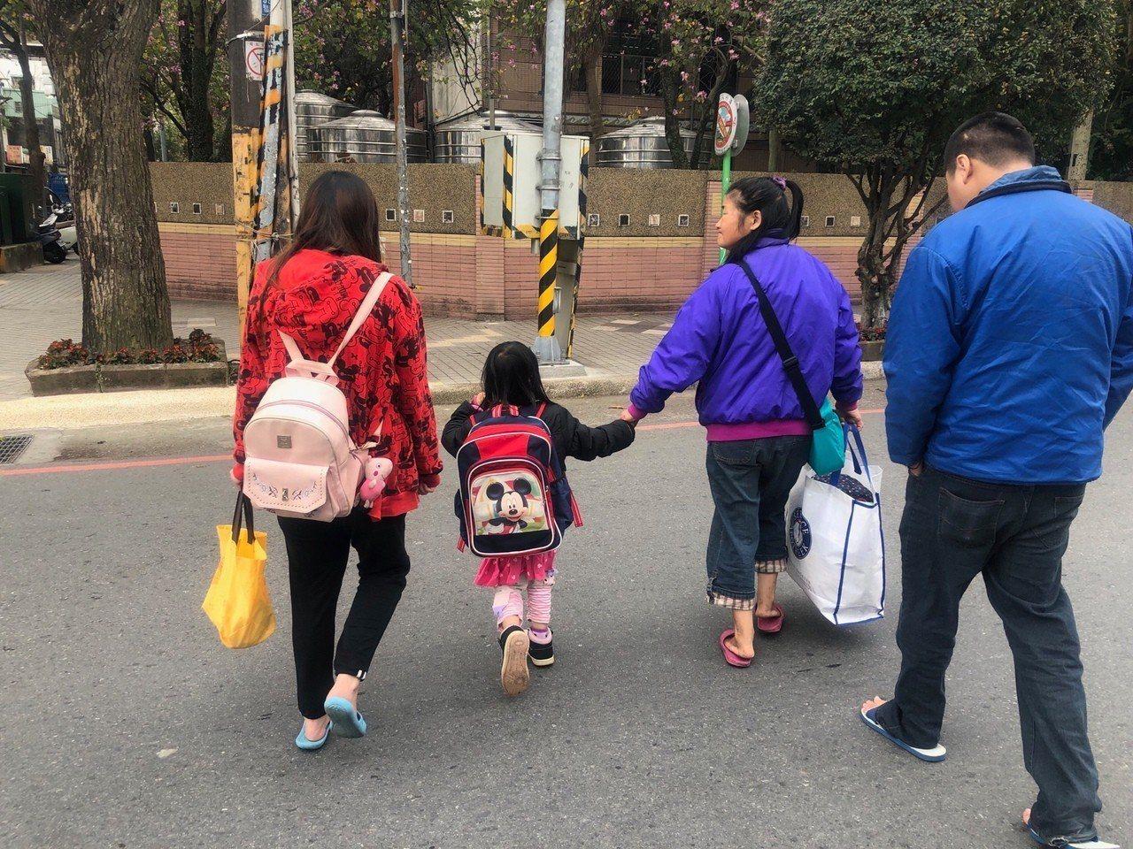 彭婦(右2)牽著綺綺(左2)的手,在她爸媽陪伴下一起到學校註冊。記者曾健祐/攝影