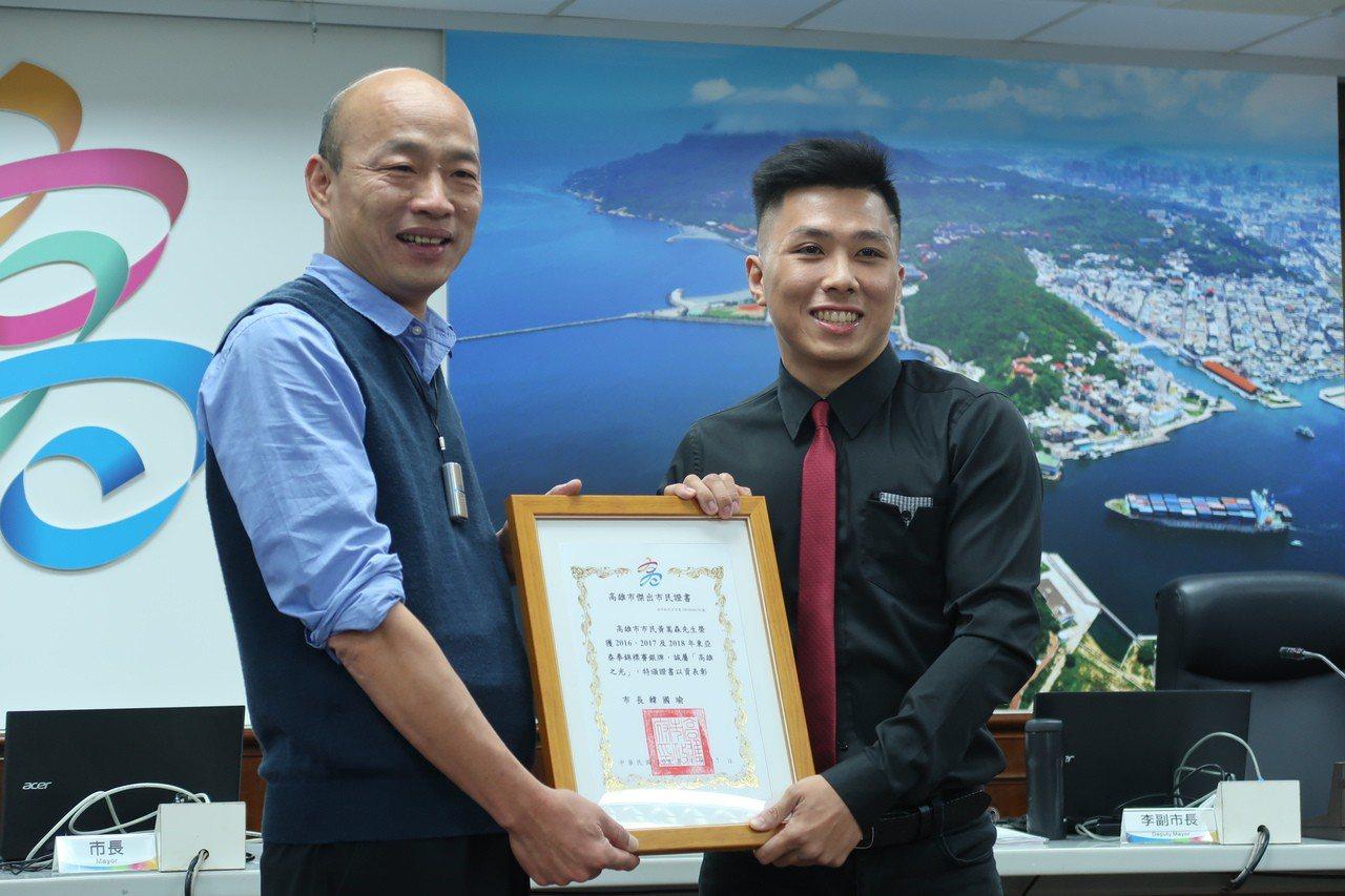 泰拳選手黃嵩森(右)從市長韓國瑜手中,接過「傑出市民證書」。記者徐如宜/攝影