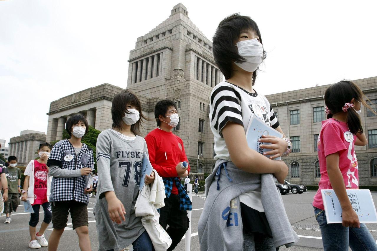 日本流感疫情為近20年來最嚴重,東京街上的學童都戴上口罩。(路透)