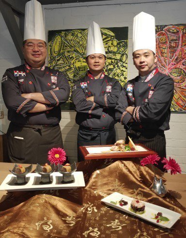 元培餐管系老師陳麒文與選手在作品前合影。 元培/提供