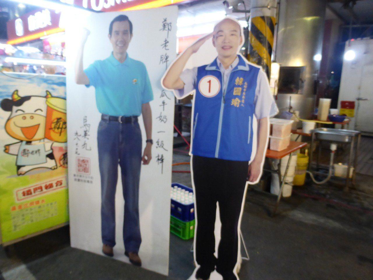 高雄市六合夜市店家擺了高雄市長韓國瑜(右)和前總統馬英九的人形立牌招徠顧客。記者...