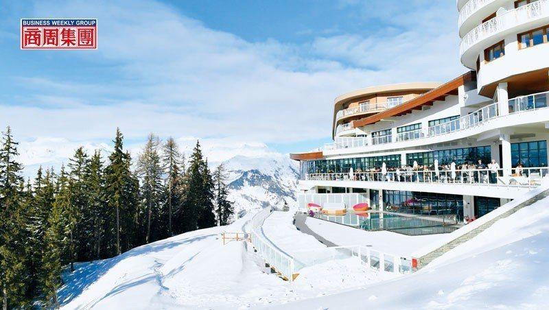 呈流線型外觀設計的度假村沿雪坡興建,旅客在露台欣賞環繞雪景。(來源.Club M...