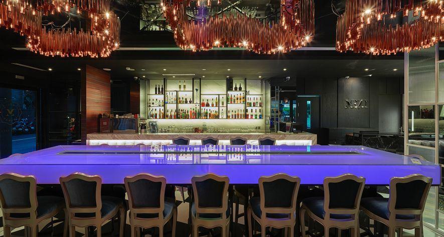 (圖)色彩變換的螢光長桌為酒吧空間形塑迷幻感。