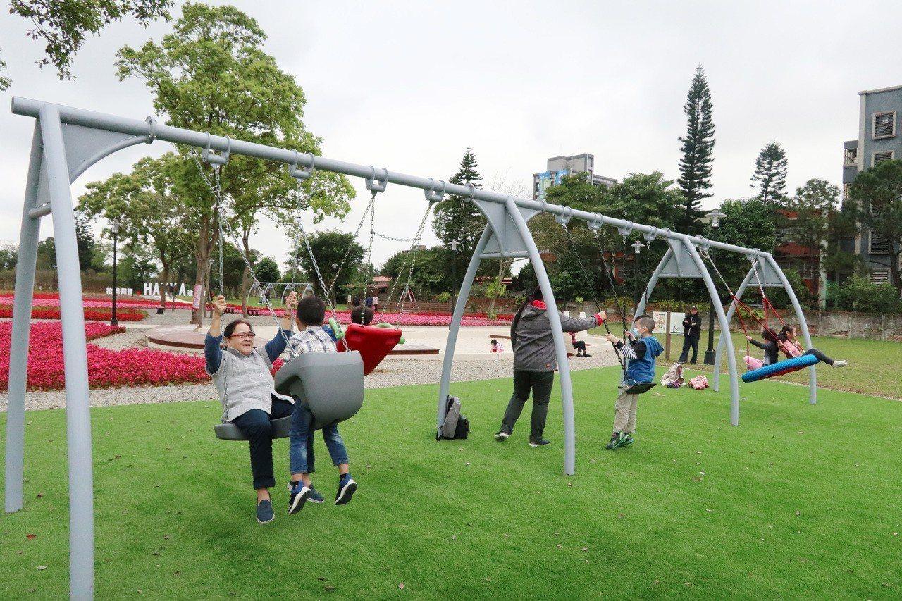 桃園市八德「花舞霄裡」公園,工務局開闢適合多齡共遊的共融式遊戲場,可見親子鞦韆、...