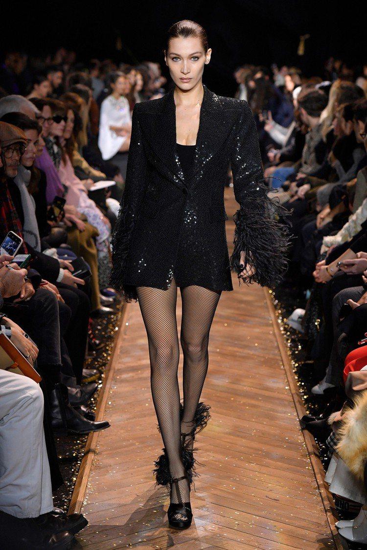貝拉哈蒂德的亮片晚裝搭配羽飾展現華麗性感的身段。圖/MICHAEL KORS提供