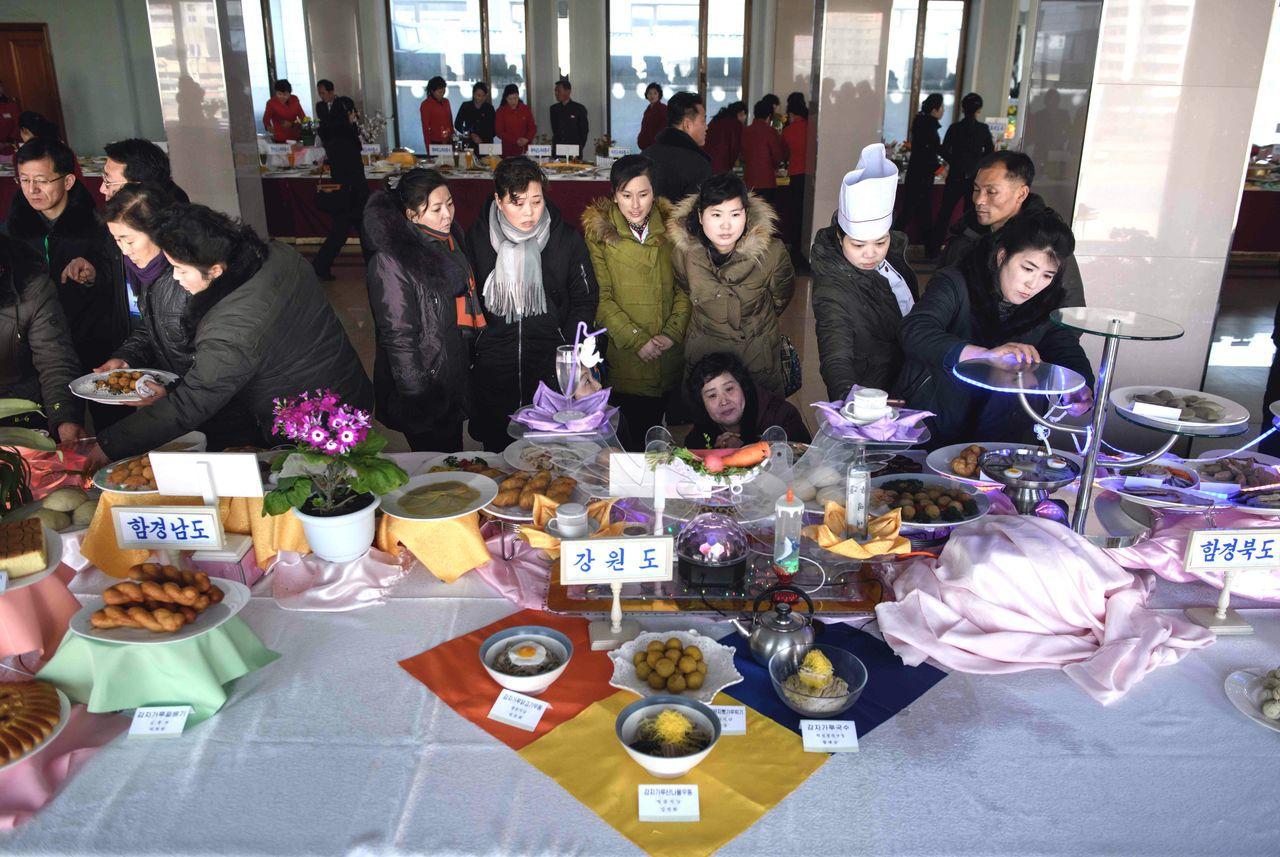 在沒有暖氣的比賽場地裡,民眾圍觀陳列在桌上的佳餚。(法新社)