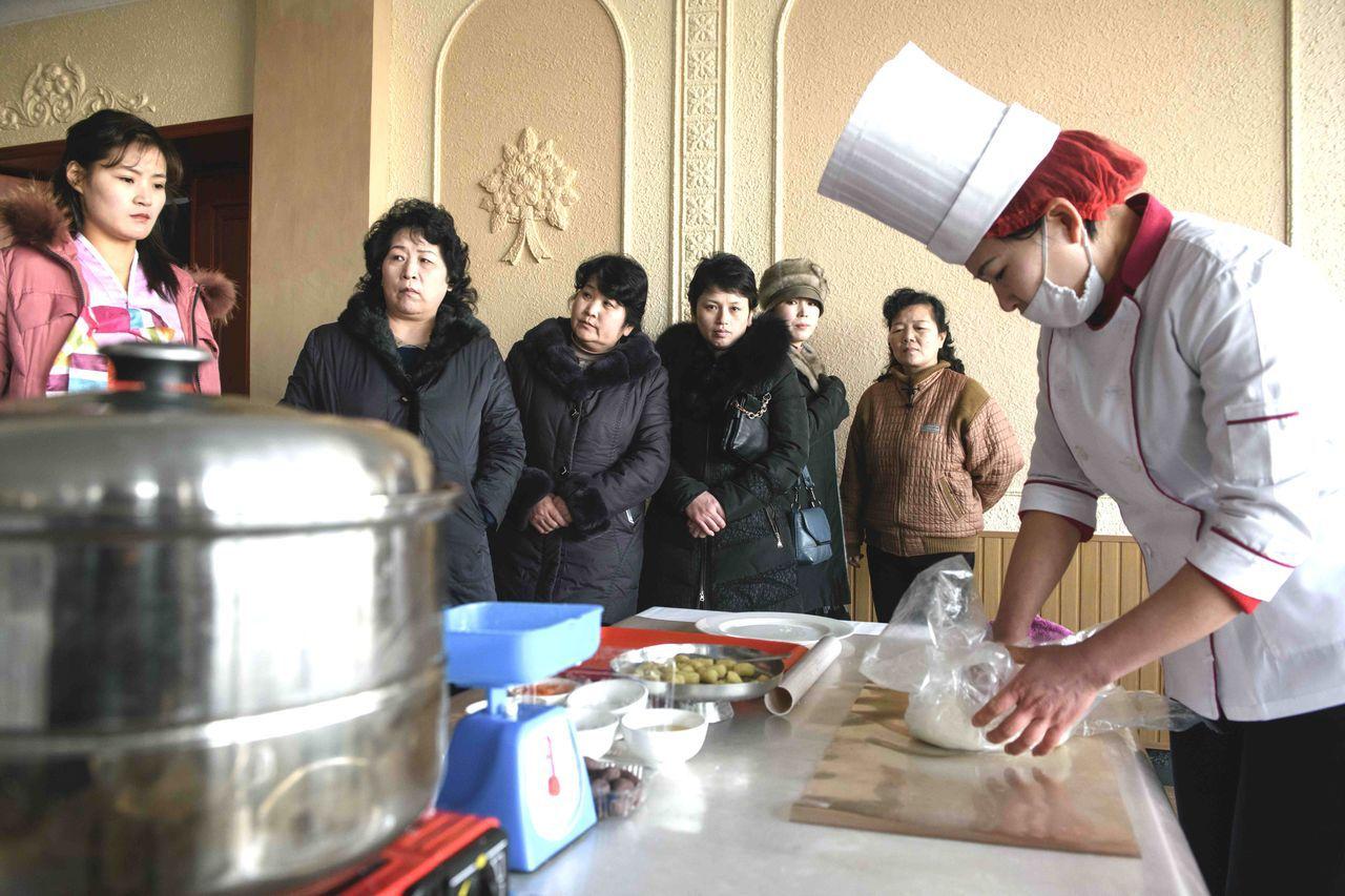 烹飪大賽裡,廚師專心製作傳統三色糯米糕。(法新社)