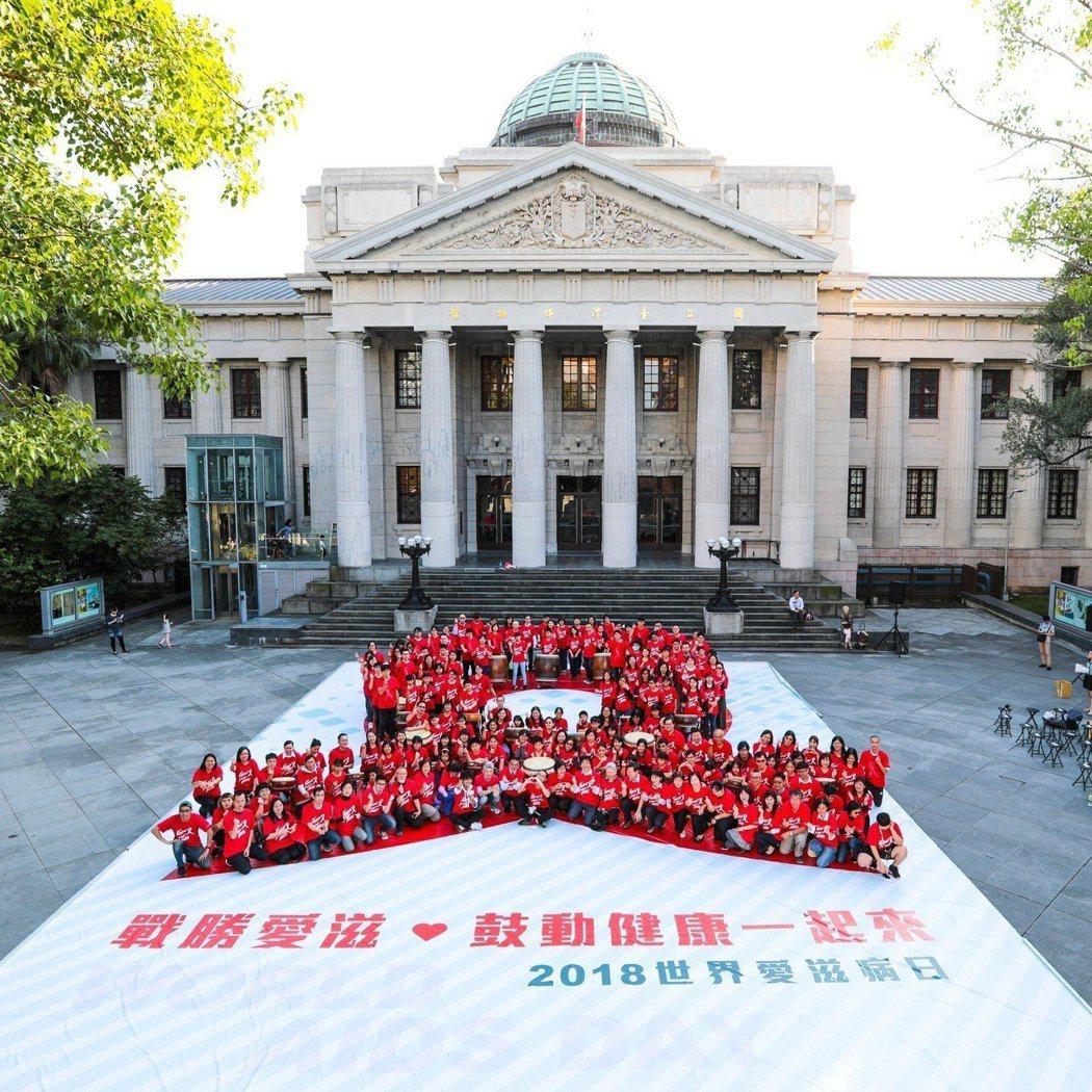 近百人去年11月30日下午於台灣博物館前廣場排成象徵「愛的開始」及「對愛滋感染者...