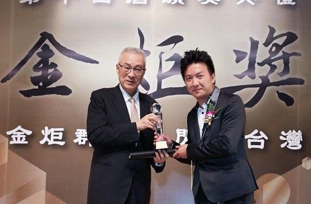 欣民國際總經理陳小醉從前副總統手中接下第14屆金炬獎座。