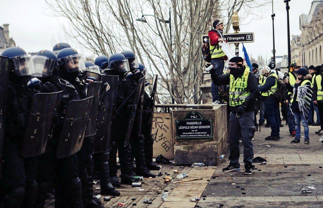 圖為一名黃背心示威者,手持催淚瓦斯的彈殼,憤怒地質問著法國鎮暴警察的執法尺度。在...