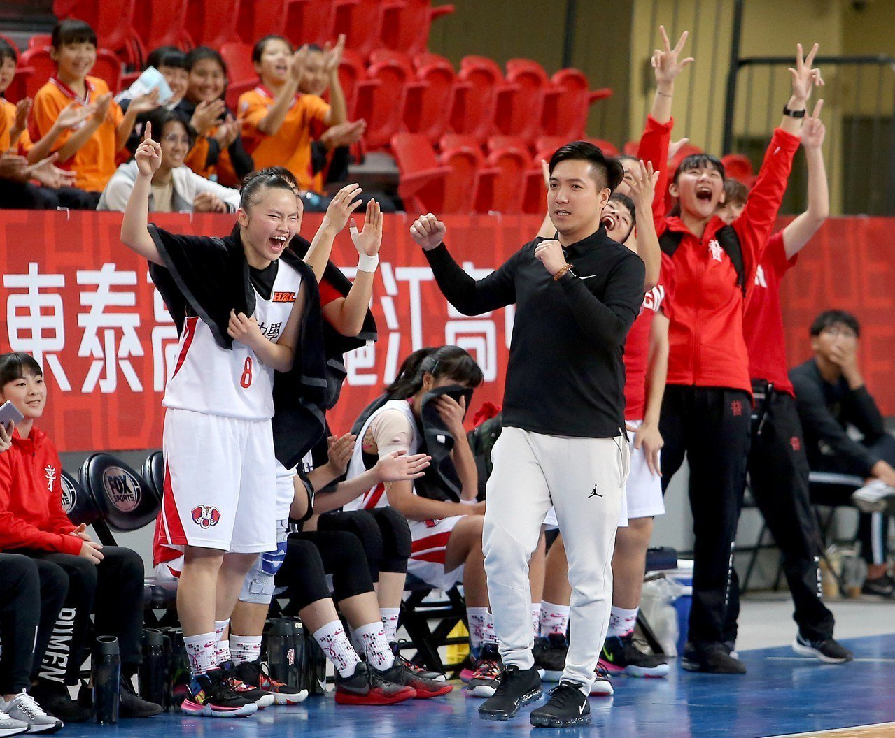 普門高中以78比58擊敗北一女中,教練廖哲億(中)與板凳席球員在場邊歡呼。 記者...