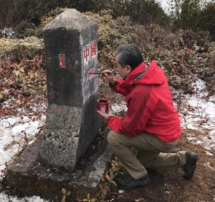 中共國務委員兼外交部長王毅勘察中緬邊界,為「共和國1號碑」描紅塗色。 (雲南外事...