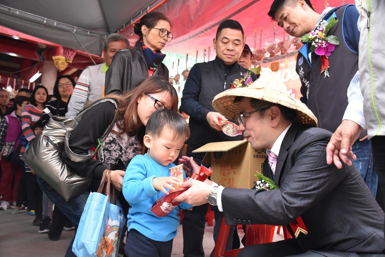 宜蘭市長江聰淵與五穀廟一起將平安五穀米與限量的翡翠琉璃豬祈福吊飾送給民眾帶回家。...