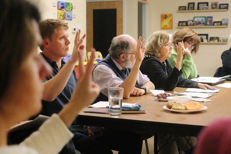 圖為美國密西根州的Newberry Place合作住宅住戶們,在參與決策會議時舉...