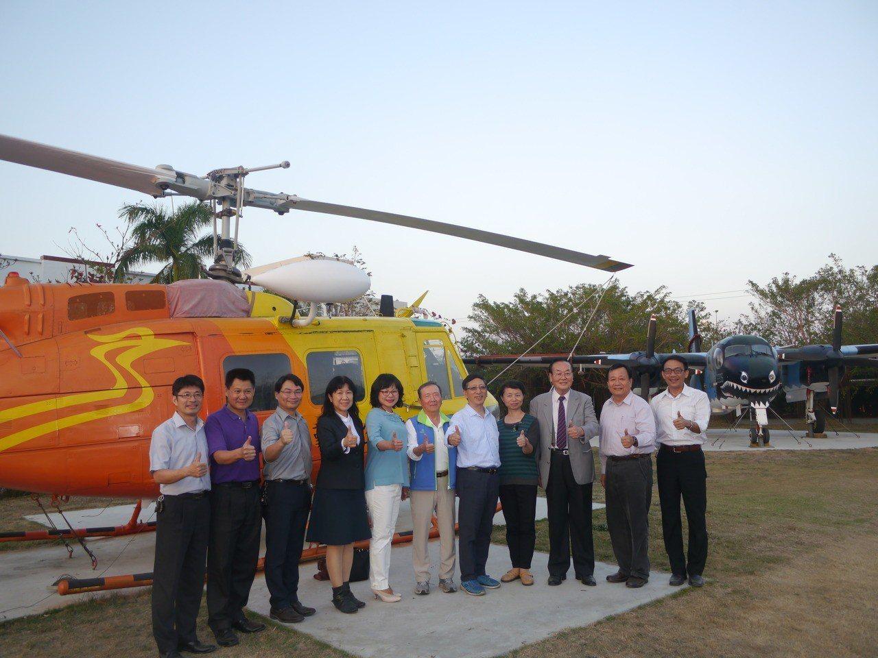 華德工家的校園有兩架退役飛機,參訪人員選在空勤總隊贈送的UH1H直昇機前合影。記...
