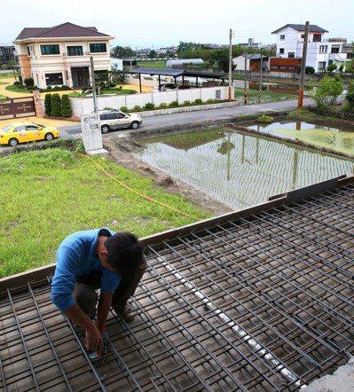 宜蘭冬山鄉,豪華農舍占據了農田,前方的工人在裝修興建中的農舍。圖/報系資料照