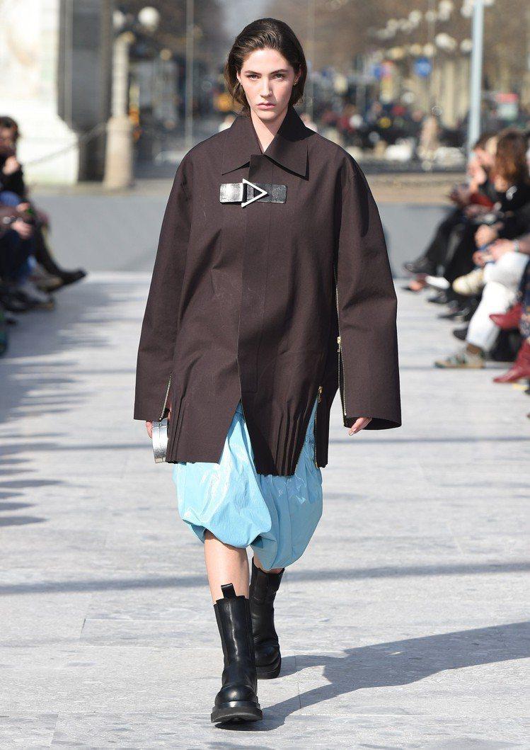 大衣下擺的百褶與花苞裙擺也透過直身線條和分量感交錯混合出獨特性格。圖/Botte...