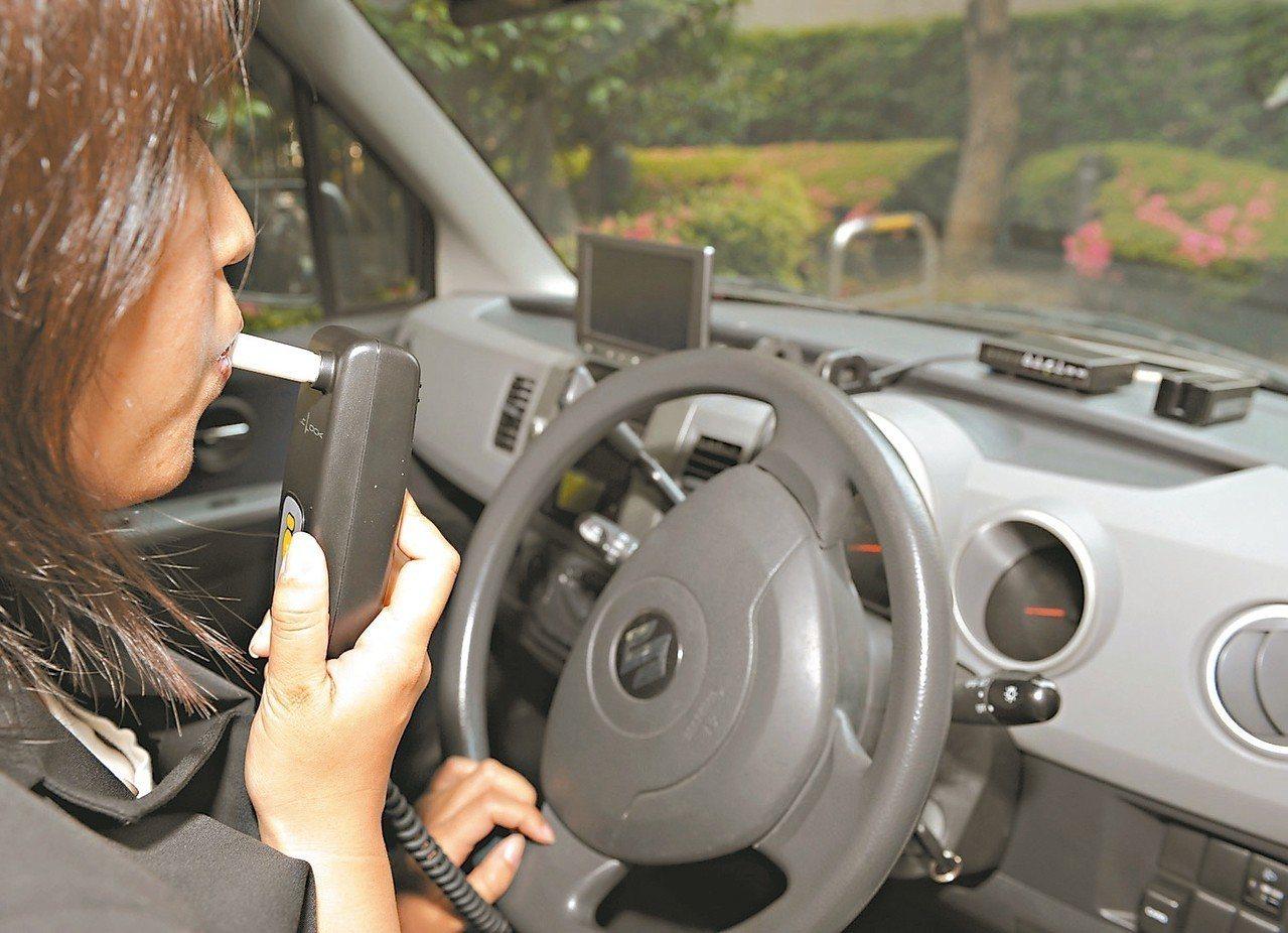 日本東海電子員工示範須先呼氣酒測才能發動的「酒精鎖」。 (法新社)