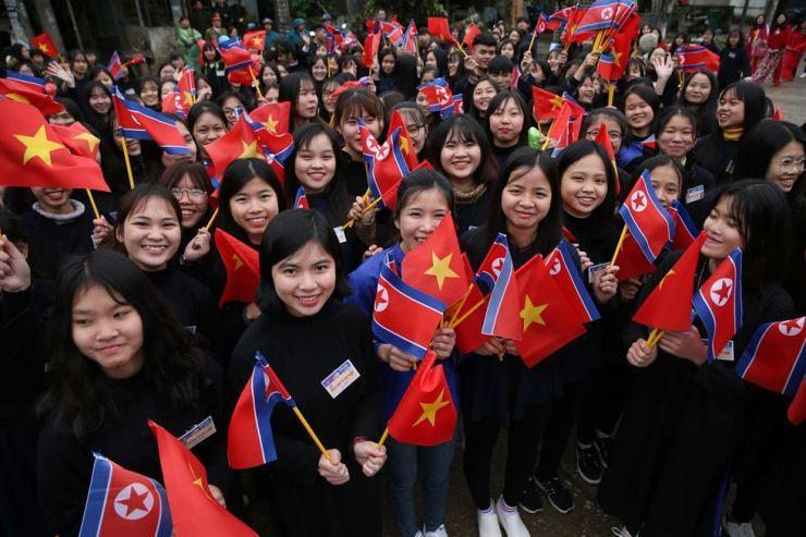 同登站外聚集大批人潮,手持越南與北韓國旗歡迎金正恩。 (路透)