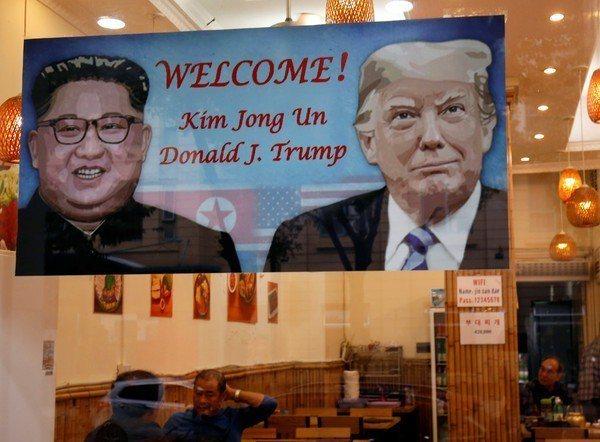 河內一間餐廳高掛川普和金正恩的海報,迎接川金二會登場。路透
