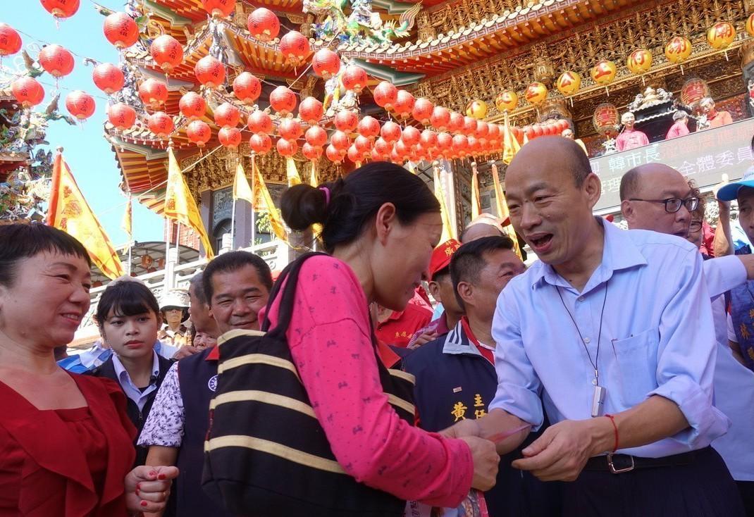 新春期間,韓國瑜(右一)走訪全市宮廟發紅包,不時有民眾高喊「選總統」。 圖/聯合...