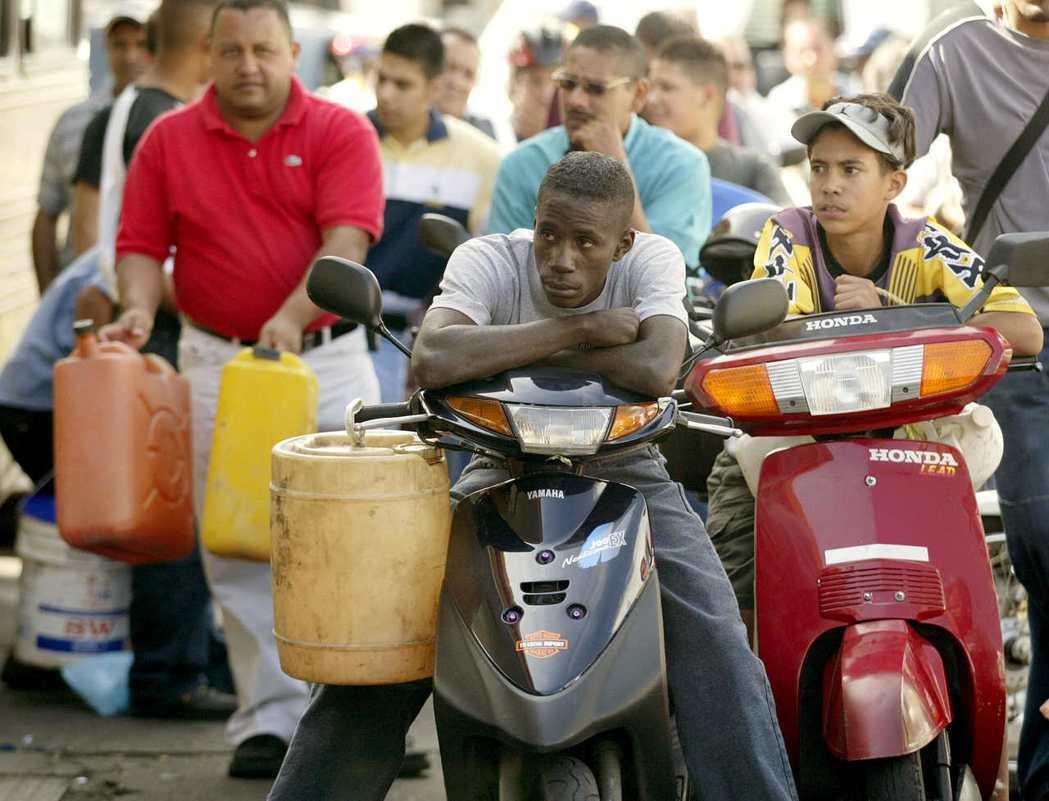 2002年那一場大罷工,造成石油減產。圖為當時等著加油的委內瑞拉民眾。 圖/路透...